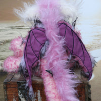 Clarissa The Candyfloss Mountain Dragon a wild yet calm and feminine fluffy pink dragon in gorgeous mohair and faux fur by Barbara Ann Bears, she stands 15 inches( 38 cm) tall and is 11.5 inches (29 cm) sitting. She is about 20 inches (50cm) from nose to tail and has a wingspan of 16 inches (40cm).