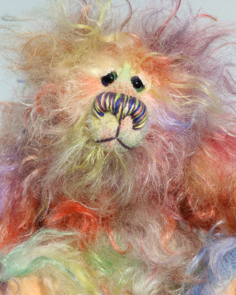 Dear Prudence, a bright and friendly, one of a kind, artist teddy bear by Barbara-Ann Bears, she stands 8.5 inches( 21 cm) tall and is 6.5 inches ( 16 cm) sitting.  Dear Prudence is made from a very long and twirly mohair that Barbara has dyed in oranges, greens, blues, reds, yellows, maroons, purples and lilacs