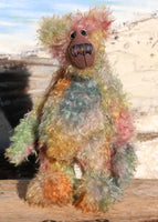 Emerson Ploom an elegant colourful, one of a kind, hand dyed mohair artist bear by Barbara-Ann Bears. He stands 16.5 inches (42 cm) tall and is 13 inches (33 cm) sitting and is made from long distressed mohair hand dyed in greens, blues, ambers, pinks, oranges, golds and lilac, the backcloth has been dyed a dull mauve