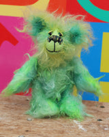Freddo is a wonderfully happy and gorgeously green, one of a kind artist teddy bear by Barbara-Ann Bears in long and fluffy hand dyed mohair, he stands just 7.5 inches( 19 cm) tall and is 5.5 inches ( 14 cm) sitting.  Freddo is mostly made from a long distressed tousled mohair dyed jade, lime, emerald and bottle green