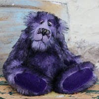 Griswald Grooch is made from a straight pile, medium length, black-tipped purple mohair that on a little bear seems quite long and fluffy. Griswald has purple velvet paw pads which complement his mohair beautifully and have a slight sparkle.  Griswald Grooch has beautiful, hand painted eyes with hand coloured eyelids, a splendid little nose embroidered from individual threads to match his colouring and he has a sweet, friendly expression