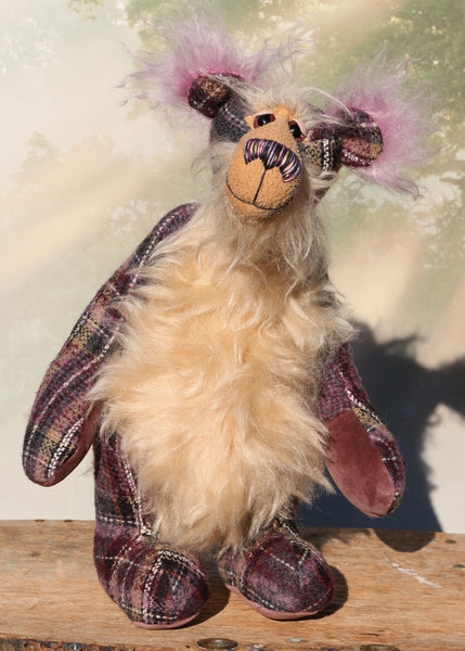 Maevis is a rather refined, loving and gentile one of a kind moahir artist bear by Barbara Ann Bears, she stands 15 inches( 38 cm) tall and is 12 inches (30 cm) sitting. Maevis is  from a beautiful 'tweedy' tartan in mauve, purple, gold, white, cream and grey, contrasted with a very long and soft wavy beige mohair.
