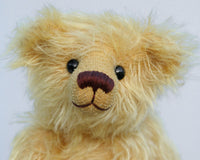 Marigold's Teddy is made from gorgeous slightly distressed golden blond German mohair, he has old, black boot buttons for eyes and beige wool felt paw pads. He has a pert, little, carefully embroidered brown nose and the sweetest smile