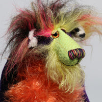 Mister Oofaloosy's face is made from long hand dyed mohair hand dyed lime green, the top of his head and the backs of his ears are a very long, black, pink and yellow faux fur and the fronts of his ears are a short, black spoted white animal print faux fur, he has beautiful, sparkling, hand painted glass eyes with hand coloured eyelids, a beautiful nose embroidered from individual threads to match his colouring and a sweet, enchanting smile