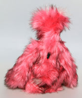 Pink Plink Fizz is an exceedingly cuddly, pink and fluffy, one of a kind, artist bear by Barbara-Ann Bears in luxurious mohair and faux fur, he stands 15 inches (38 cm) tall and is 12 inches (30 cm) sitting. He is made from a long, dense and soft faux fur which is a very strong pink with subtle black tipping.
