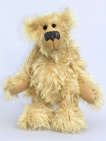 Scraggly Scratchit is a friendly, cuddly and extremely shaggy, one of a kind mohair artist bear by Barbara Ann Bears in scraggly golden mohair Scraggly Scratchit stands 13.5 inches(34 cm) tall and is 10.5 inches (26 cm) sitting.  Scraggly Scratchit is a wild and shaggy chap with a rather sad but hopeful expression