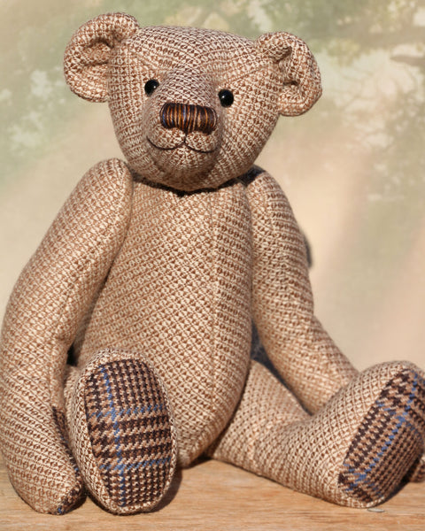 Tweedy is a an elegant and refined traditional Barbara Ann Bear made in a very dapper tweed from tweed maker Romney Tweed, he is 16 inches (38cm) tall and is 11 inches (30cm) sitting. Tweedy is made from tweed with a golden brown and creamy beige pattern his paw pads are tweed, in a brown, beige and blue tartan