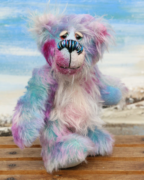 Tim Pimpling is a happy, little one of a kind, mohair artist bear by Barbara-Ann Bears. Tim stands 6.5 inches( 16 cm) tall and is 5 inches ( 13 cm) sitting. He is mostly made from a medium length, slightly distressed and fluffy mohair that Barbara has hand dyed in sky blue with some splashes of magenta, pink and lilac
