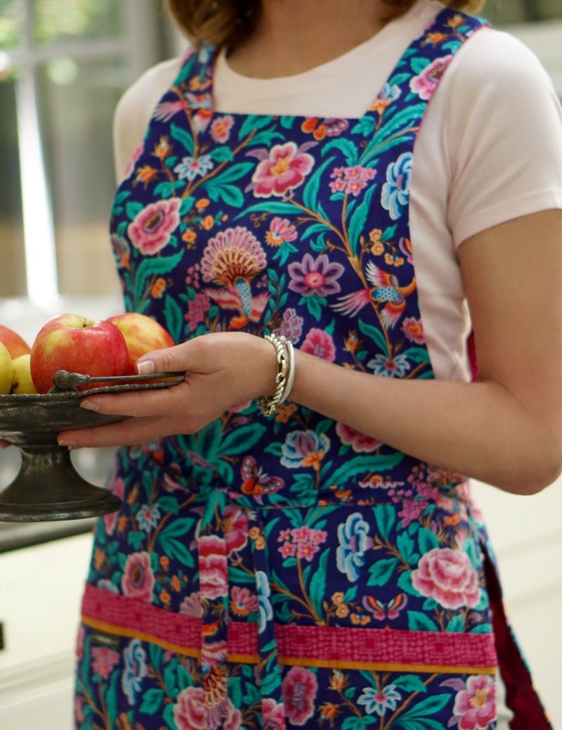 Woman wearing a cute fashion apron in a birds and flowers print in bright blue and hot pink holding a plate of apples.