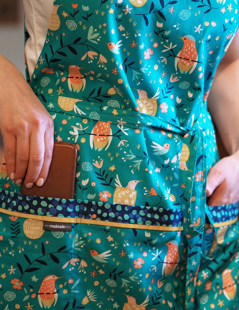 Woman wearing a cute kitchen apron in a print of humming bird, flowers and dots reversing to a dot print in a combination of turquoise, navy, orange and yellow, bird print side showing specially designed pockets perfect to fit a cell phone and more.