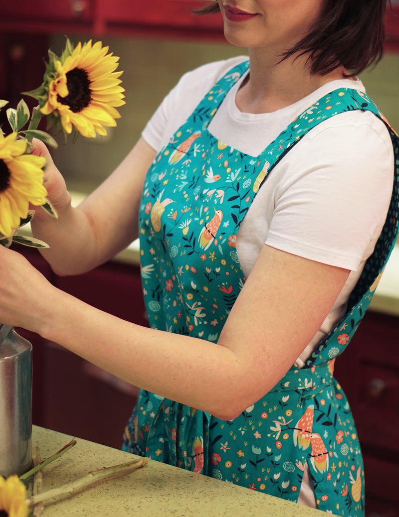 Woman arranging sunflowers wearing a cute kitchen apron with pockets in a humming bird, flowers and dots print reversing to a dot print in a combination of turquoise, navy, orange and yellow, bird print side.
