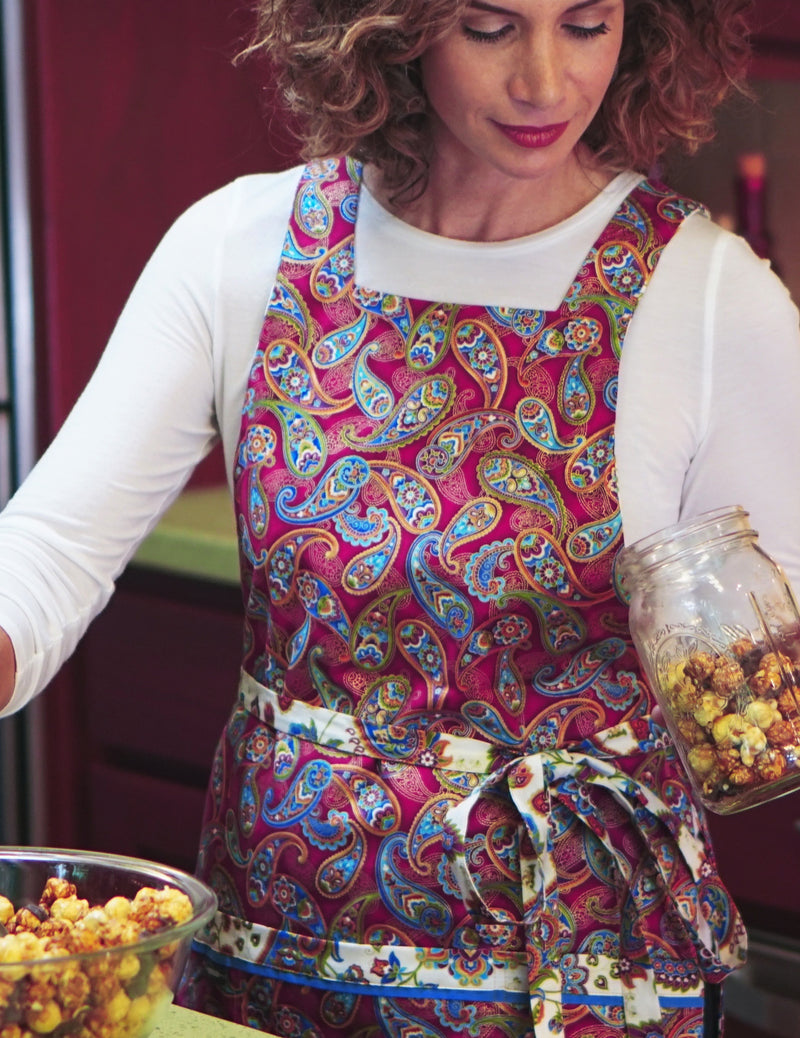 Woman preparing holiday food gifts wearing a paisley and medallion print apron in berry, ivory and cerulean enhanced with metallic gold accents, berry paisley print side.