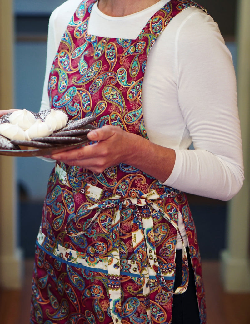 Woman holding a plate of holiday cookies wearing a paisley and medallion print apron in berry, ivory and cerulean enhanced with metallic gold accents, berry paisley print side.