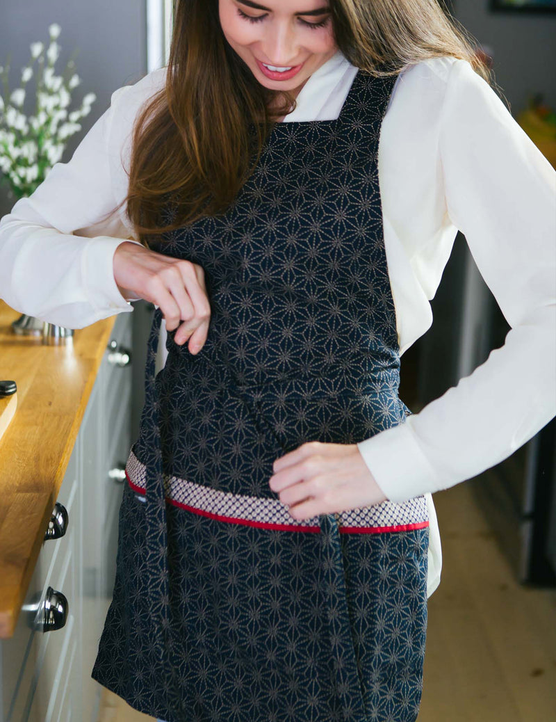 Woman tying a Japanese apron at the waist in a print of stitched stars reversing to ikat dots in navy and ivory, stitched stars print side.