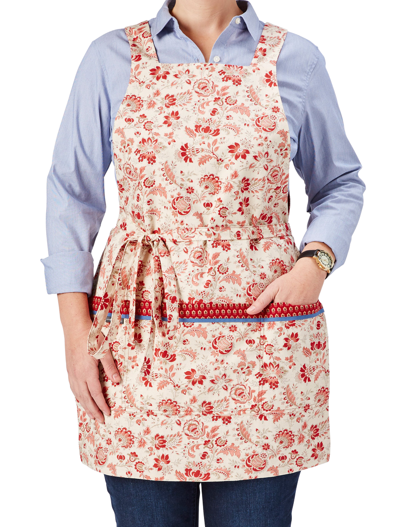 Cute kitchen apron in a French country print in red and ivory with touches of taupe, one side features red flowers on an ivory background and reverses to a tiny red floral print on the other, red floral print on ivory ground side, front view.