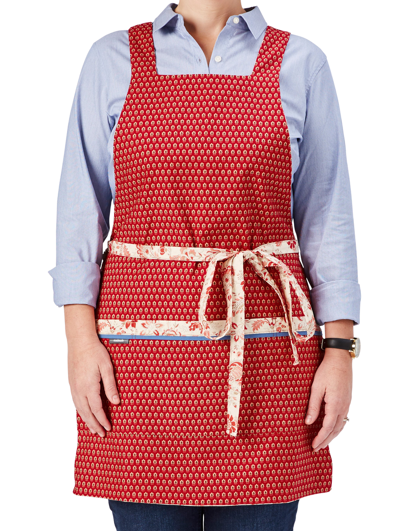 Cute kitchen apron in a French country print in red and ivory with touches of taupe, one side features red flowers on an ivory background and reverses to a tiny red floral print on the other, tiny red floral print side, front view.