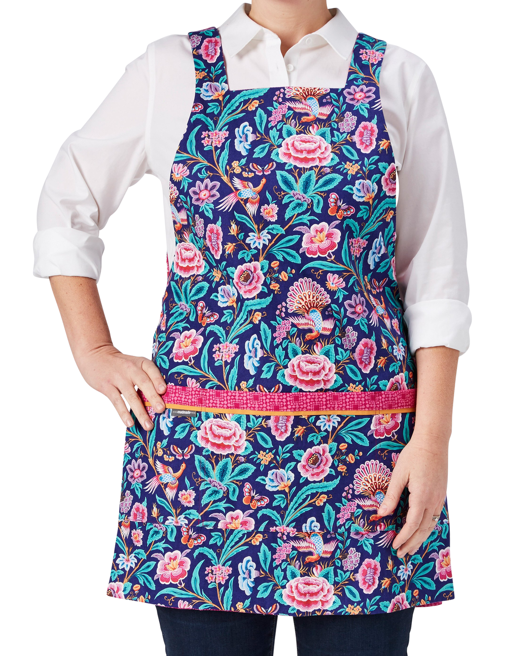 A pretty fashion apron in a birds and flowers print in bright blue and hot pink reversing to a hot pink geo print, birds and flowers print side, front view.