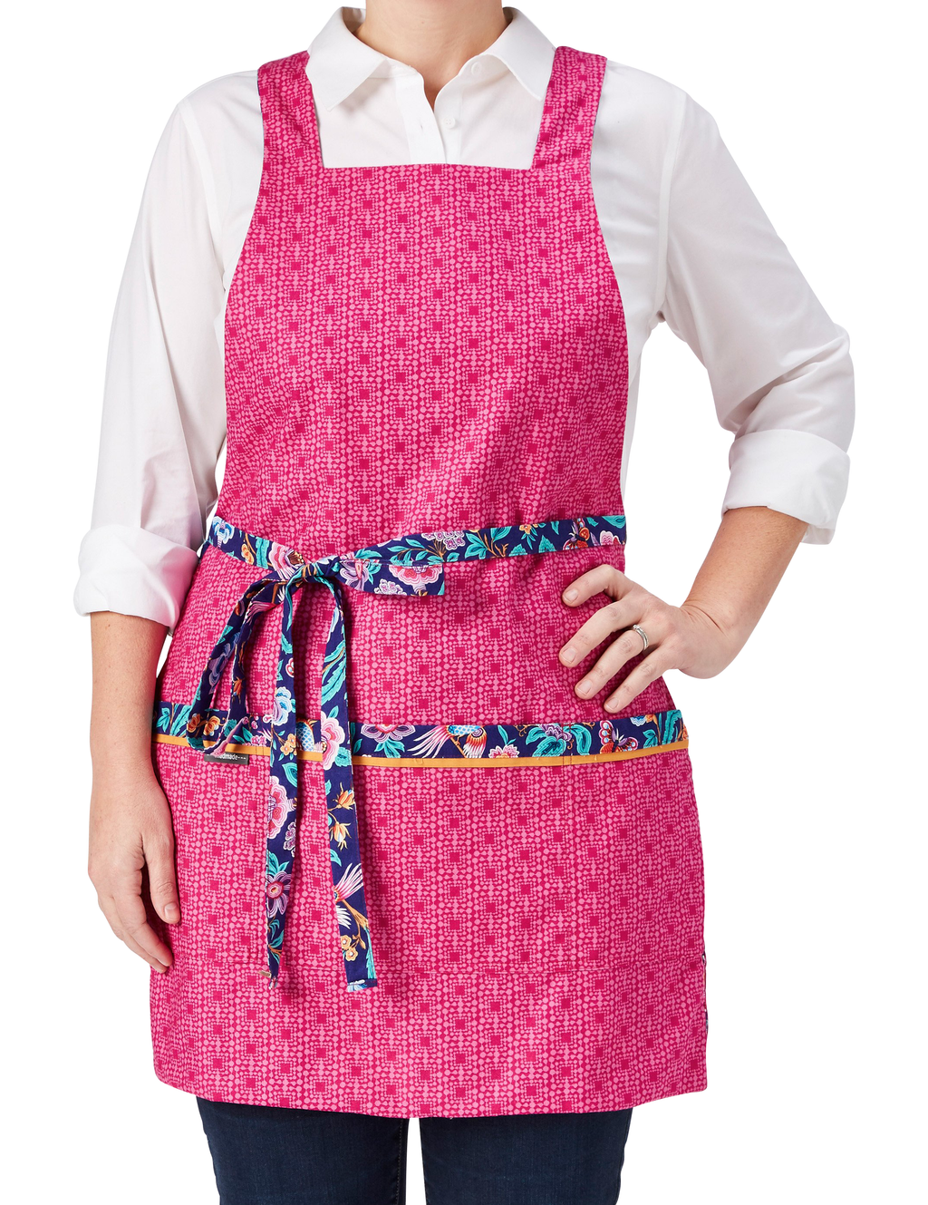 A pretty fashion apron in a birds and flowers print in bright blue and hot pink reversing to a pink geo print, hot pink geo print side, front view.