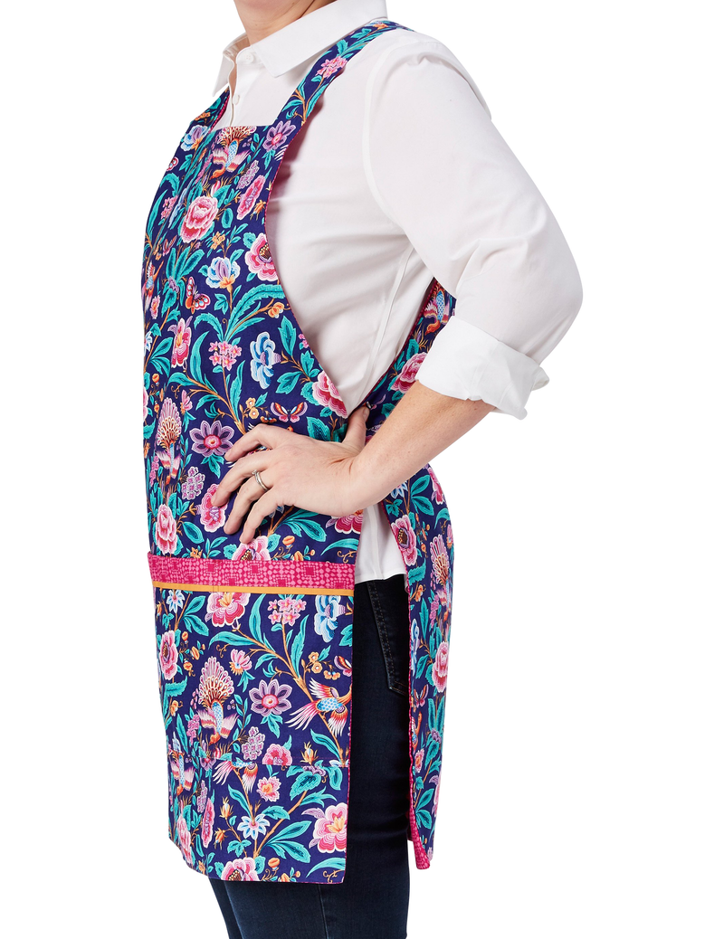 A pretty fashion apron in a birds and flowers print in bright blue and hot pink reversing to a hot pink geo print, birds and flowers print side, side view.