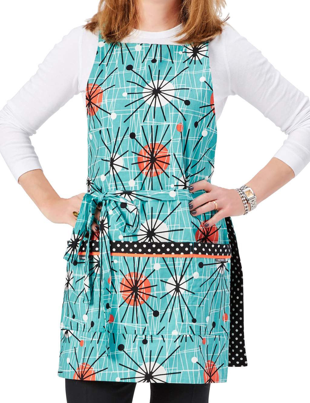 Retro apron in a Mid-century Modern abstract print in orange, black and white on a turquoise background on one side reverses to a classic black and white polka dot print on the other, turquoise abstract print side, front view.