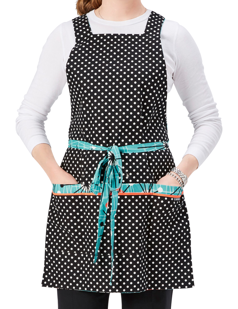 Retro apron in a Mid-century Modern abstract print in orange, black and white on a turquoise background on one side reverses to a classic black and white polka dot print on the other, polka dot print side, front view.