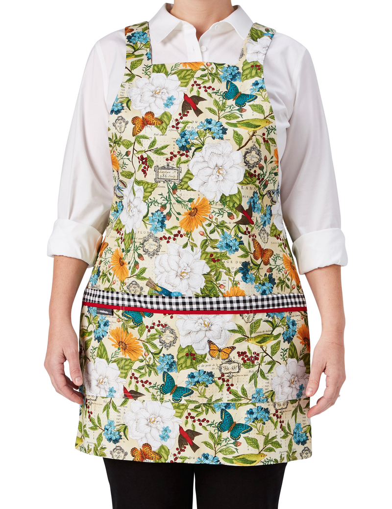 A multi-colored botanical print mixes flowers, butterflies and birds in one of our most colorful aprons, reversing to a classic black and white gingham, botanical print side, front view.