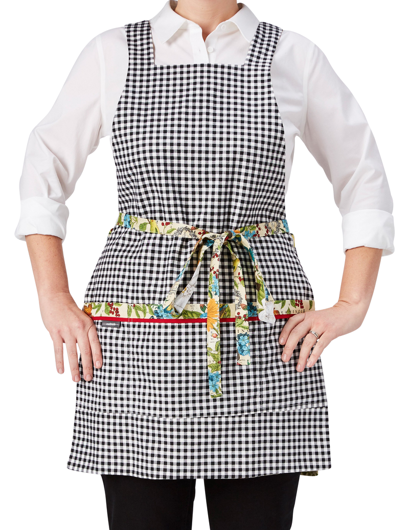 A multi-colored botanical print mixes flowers, butterflies and birds in one of our most colorful aprons, reversing to a classic black and white gingham, gingham print side, front view.