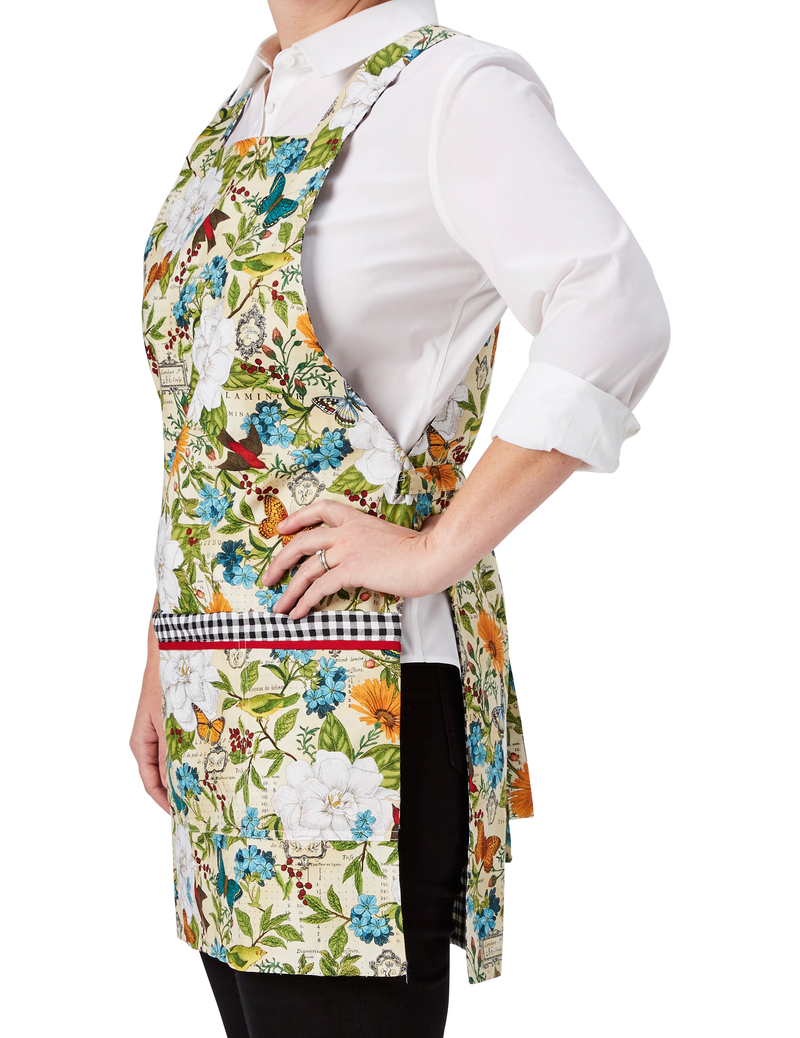 A multi-colored botanical print mixes flowers, butterflies and birds in one of our most colorful aprons, reversing to a classic black and white gingham, botanical print side, side view.