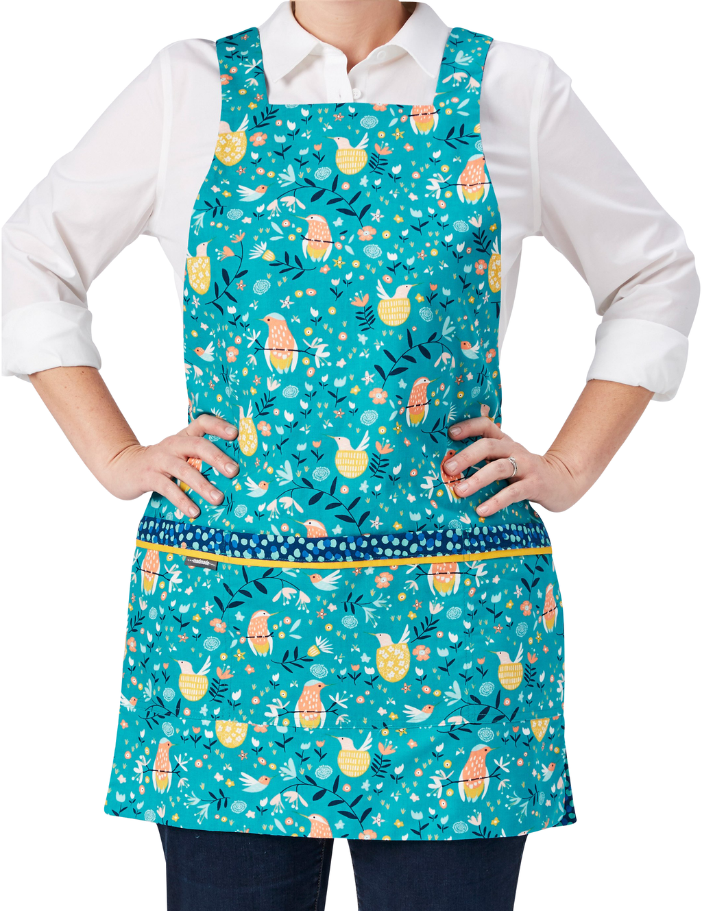 Cute kitchen apron with pockets in a whimsical print of humming birds, flowers and dots on one side, reversing to a dot pattern on the other in a combination of turquoise, navy, orange and yellow, humming bird print side, front view.
