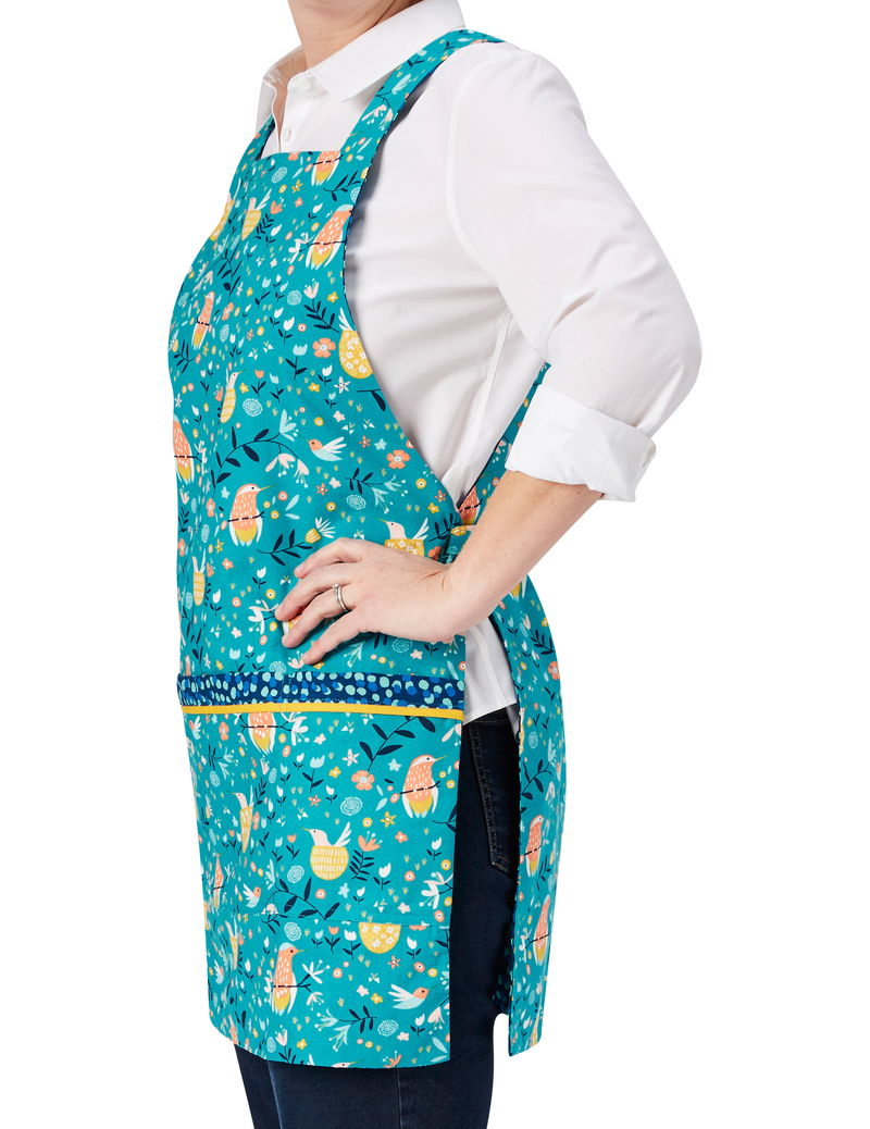 Cute kitchen apron with pockets in a whimsical print of humming birds, flowers and dots on one side, reversing to a dot pattern on the other in a combination of turquoise, navy, orange and yellow, humming bird print side, side view.