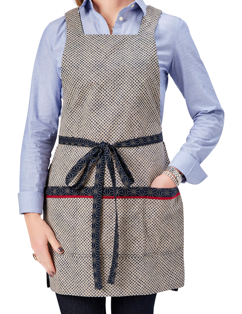 Japanese apron in a Kasuri-inspired print of stitched stars on one side reversing to an ikat dot print on the other in navy and ivory, ikat dot print side, front view.