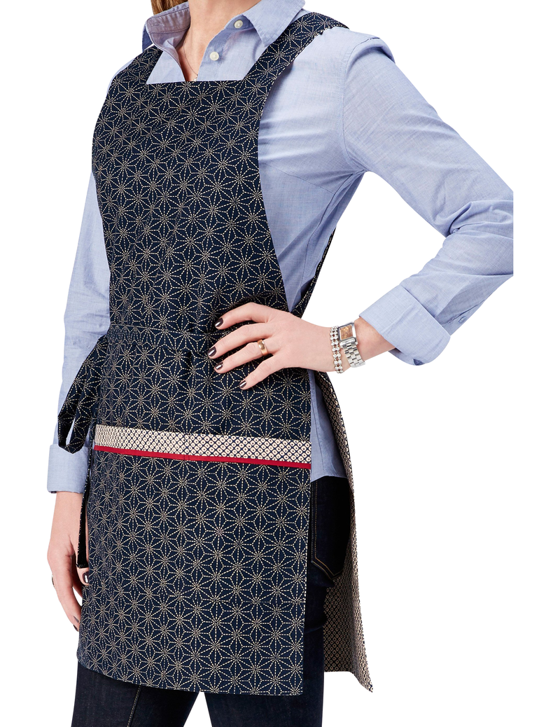 Japanese apron in a Kasuri-inspired print of stitched stars on one side reversing to an ikat dot print on the other in navy and ivory, star print side, side view.