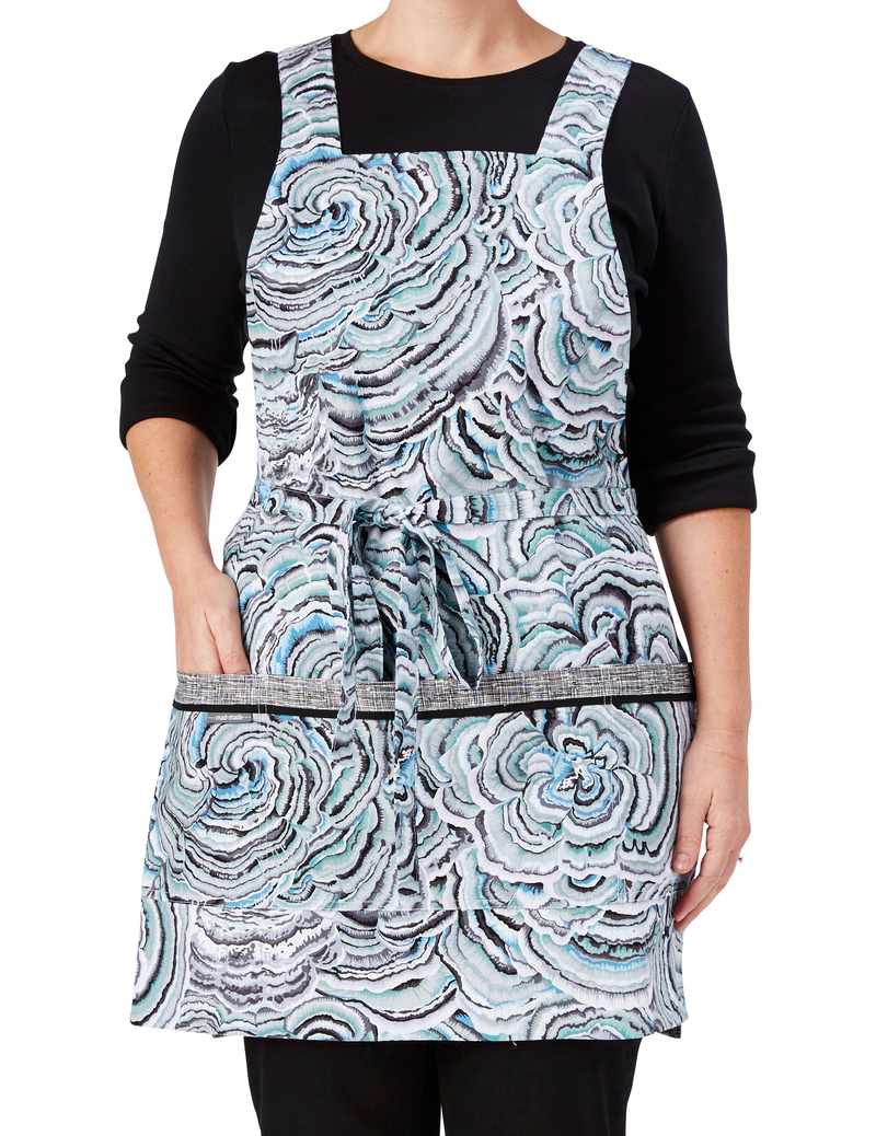 A retro apron in a print of concentric rings in soft blue and gray reversing to a black and white crosshatch print, ring print side, front view.