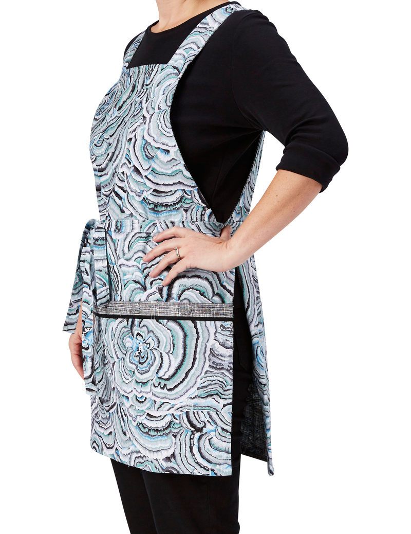 A retro apron in a print of concentric rings in soft blue and gray reversing to a black and white crosshatch print, ring print side, side view.