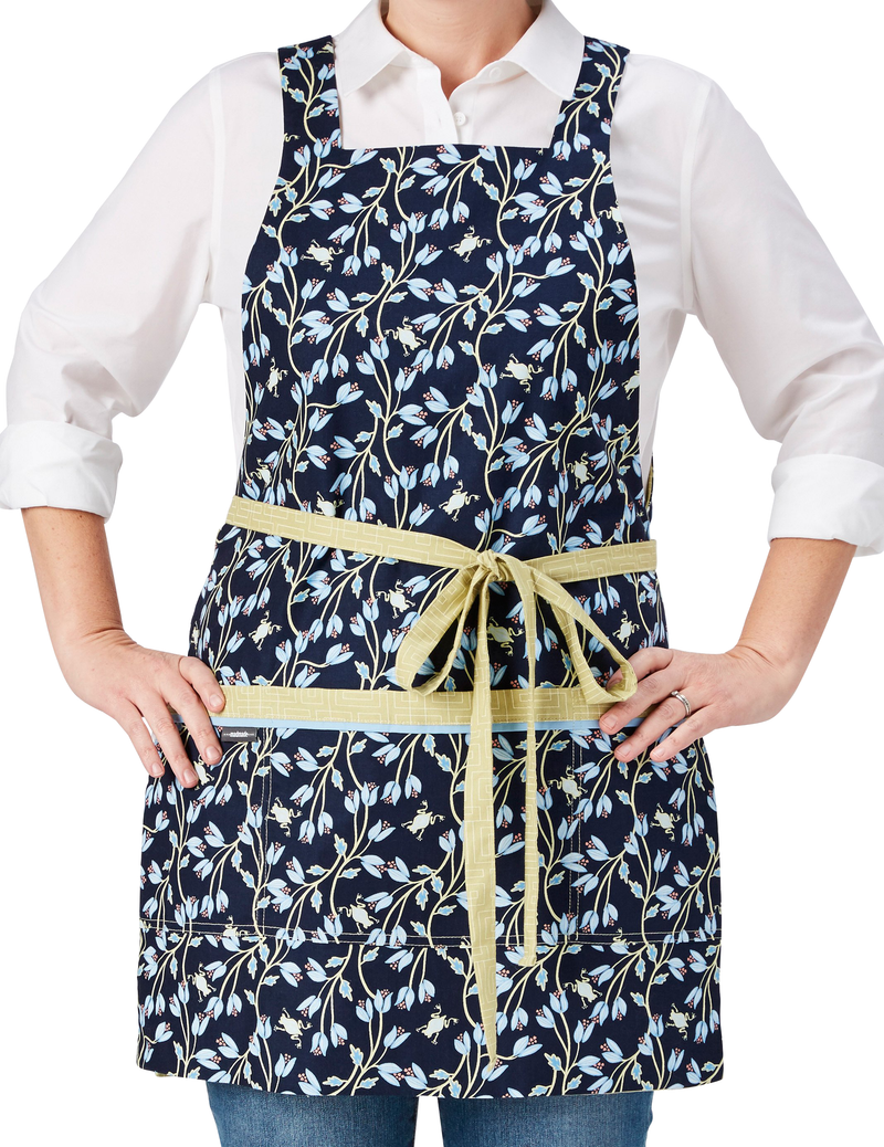 A chic and cute apron in a print of tiny frogs tucked among vines in navy and green reversing to a geometric print in soft green, navy frog print side, front view.