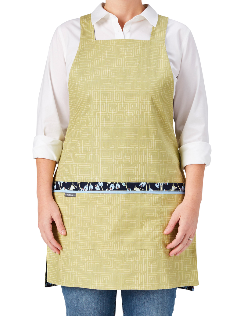 A chic and cute apron in a print of tiny frogs tucked among vines in navy and green reversing to a geometric print in soft green, soft green geometric print side, front view.