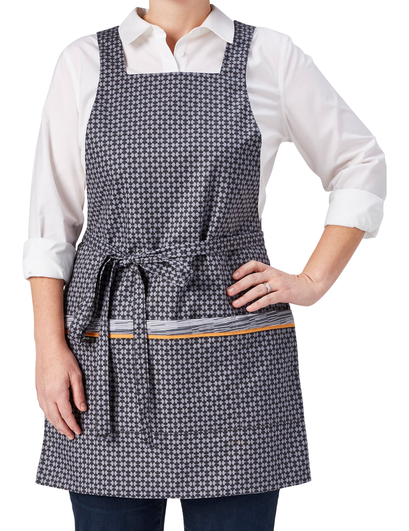 A modern apron in a subtle mix of grey geometric prints, broken stripe print in light and dark gray and white on one side reversing to a light and dark gray oval print on the other, oval print side, front view.