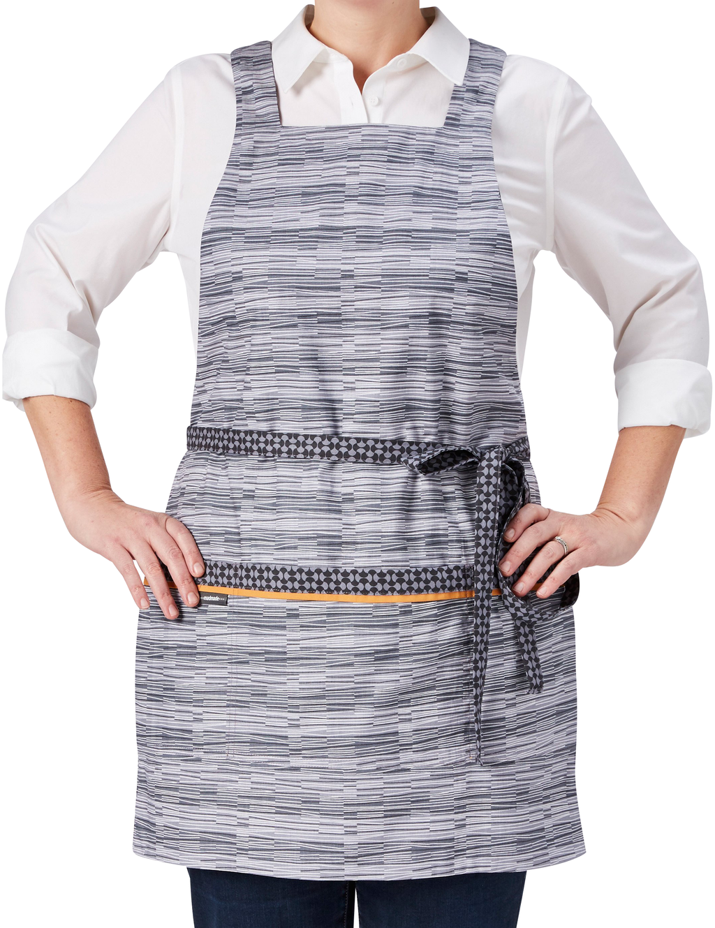 A modern apron in a subtle mix of grey geometric prints, broken stripe print in light and dark gray and white on one side reversing to a light and dark gray oval print on the other, stripe print side, front view.