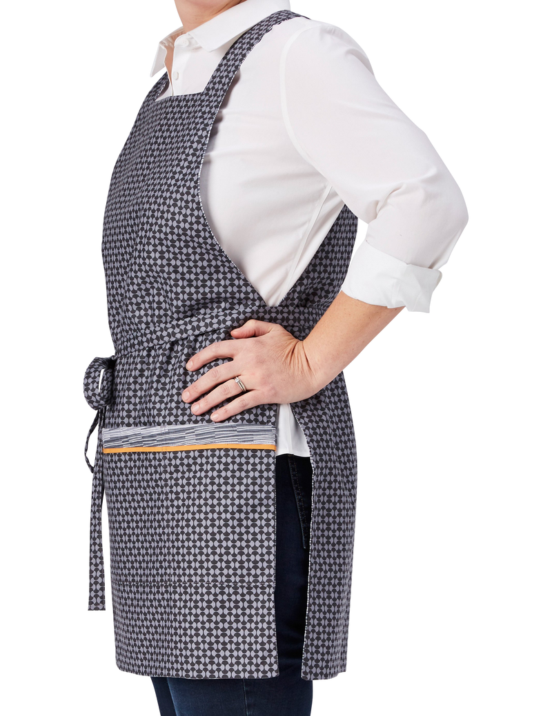 A modern apron in a subtle mix of grey geometric prints, broken stripe print in light and dark gray and white on one side reversing to a light and dark gray oval print on the other, oval print side, side view.
