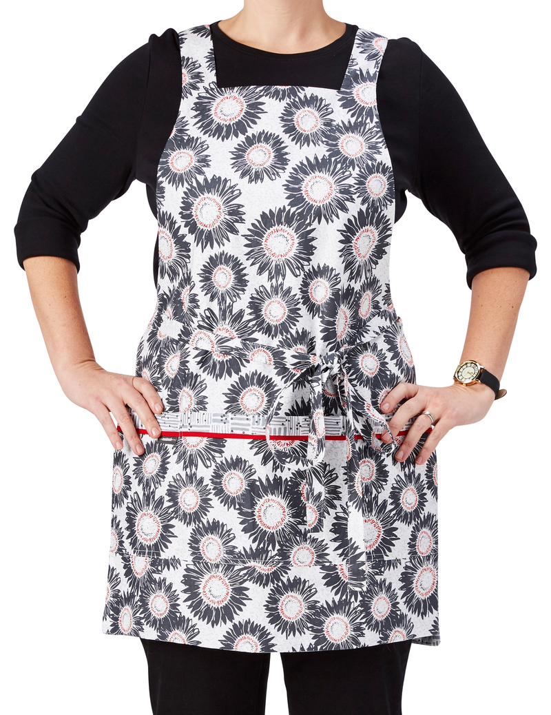 A cooking and baking apron in a sunflower print in gray, white and red on one side reversing to a Tatami-inspired print in gray and white on the other side, sunflower print side, front view.