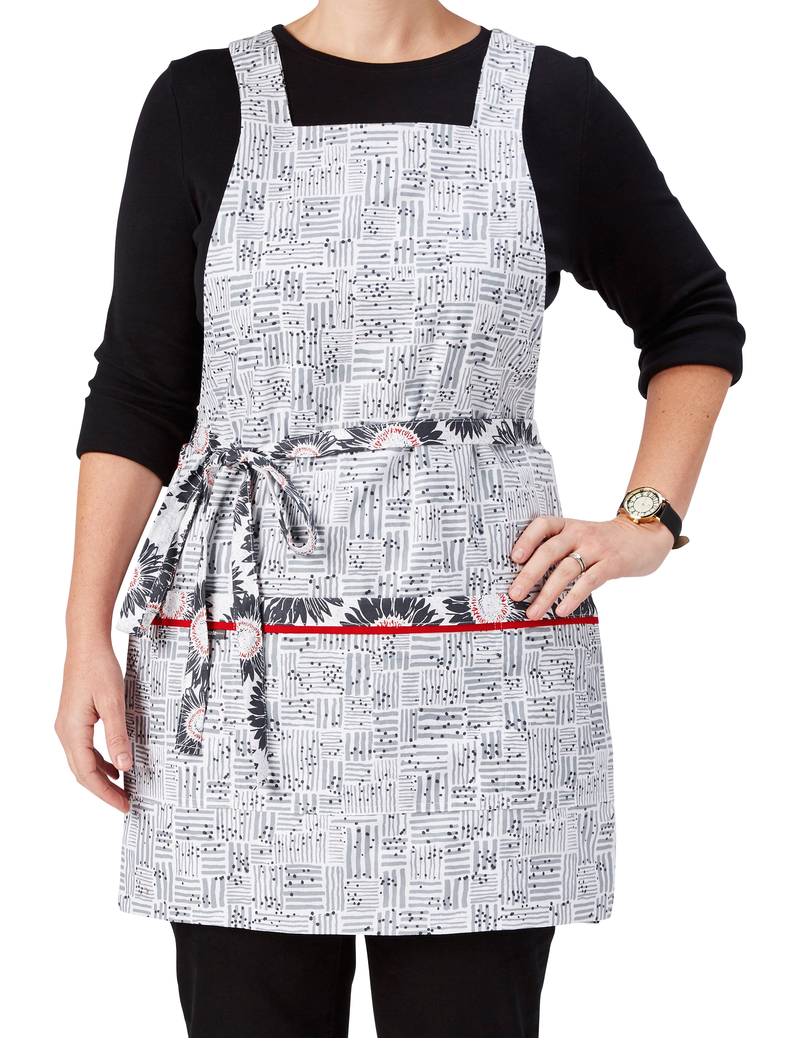 A cooking and baking apron in a sunflower print in gray, white and red on one side reversing to a Tatami-inspired print in gray and white on the other, Tatami-inspired print side, front view.