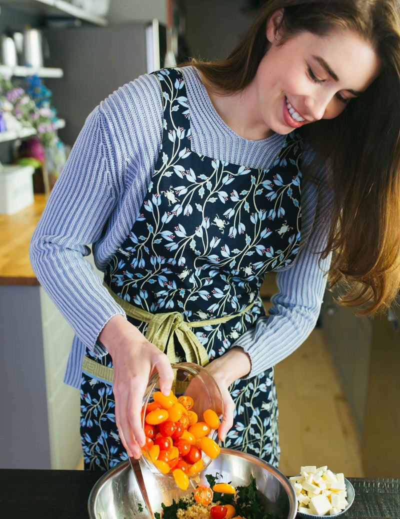 Woman preparing a meal wearing a cute apron in a print of tiny frogs tucked among vines in navy and green reversing to a soft green geometric print, navy frog print side.