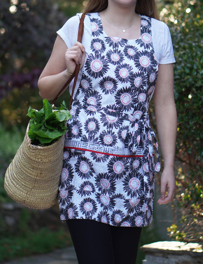 Woman carrying basket of greens wearing a cooking and baking apron in a gray, white and red sunflower print reversing to a Tatami-inspired print in gray and white, sunflower print side.