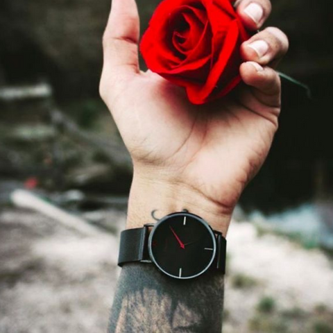 Man holding rose with black watch on