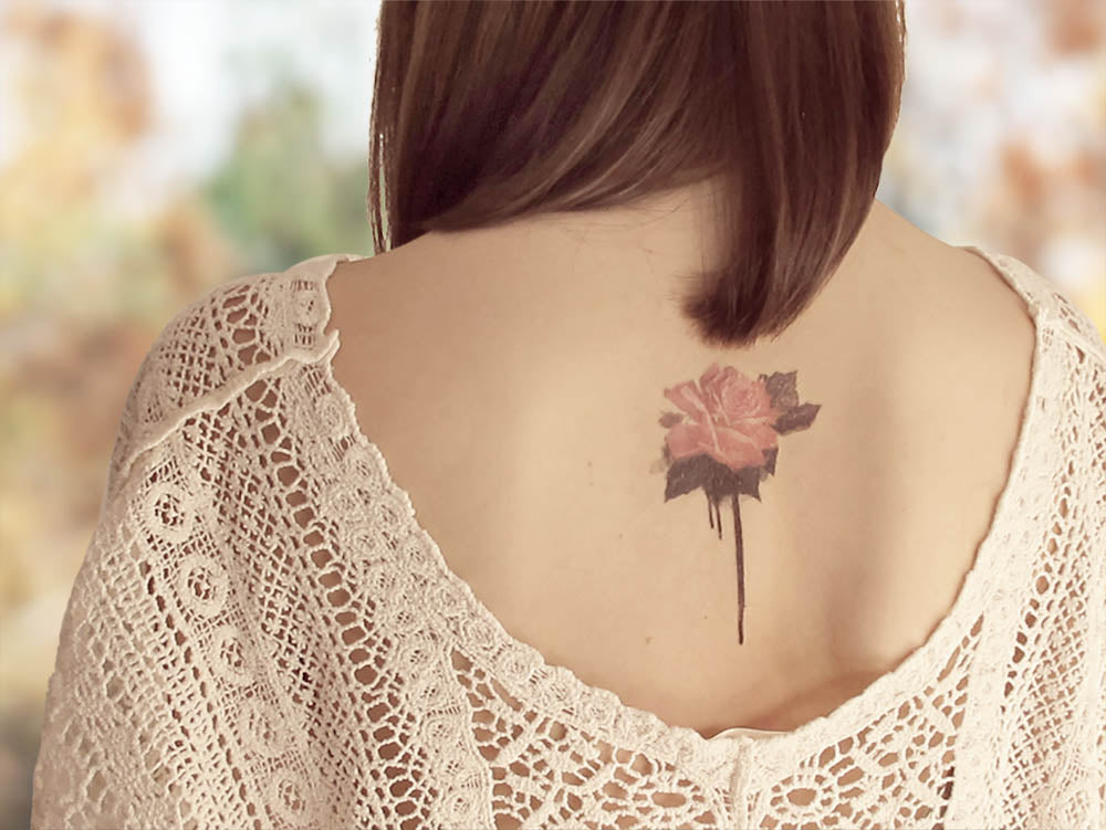 Bleeding rose designer temporary tattoo in vintage colors and black gothic leaves on girl's back