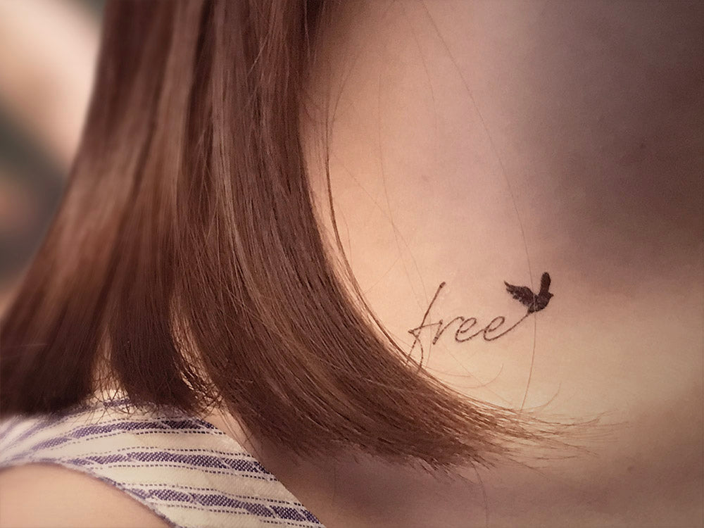Fly free as a bird small and elegant designer temporary tattoo in cursive and black silhouette