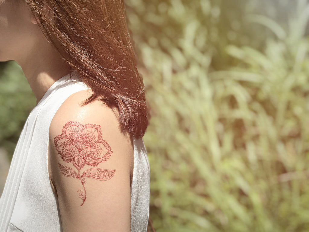 Girl with beautiful mehndi flower temporary tattoo in henna colors on the arm against nature and trees