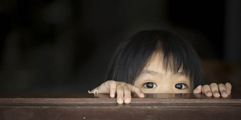 child looking through blind