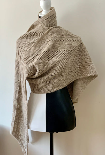 photo of moving forward shawl/wrap knit in beige heavenly blend yarn draped over a black and white mannequin