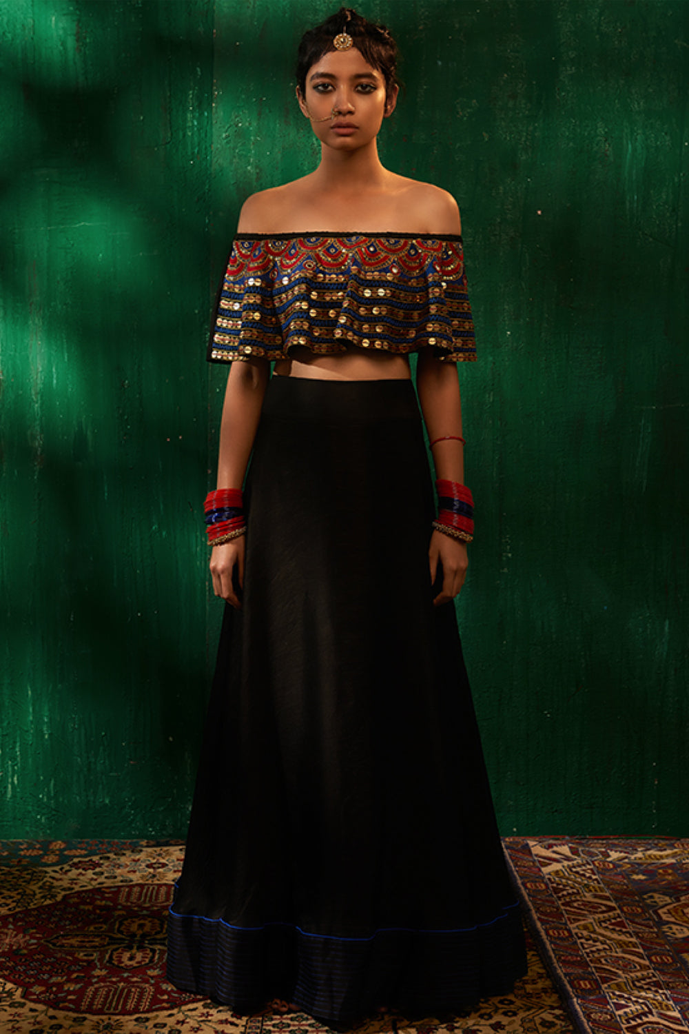 Roshni Chopra black off the shoulder top with black flared skirt.